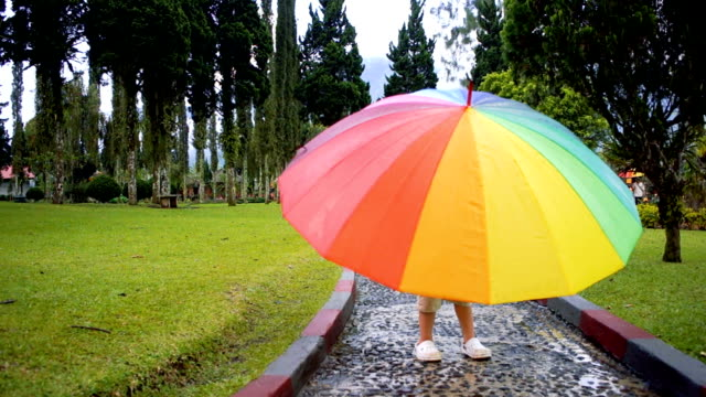 Little boy is rotating the rainbow umbrella video