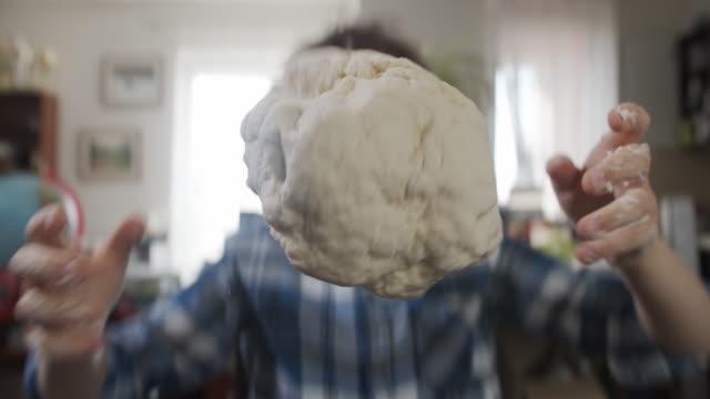 vídeos de stock e filmes b-roll de little boy is throwing the dough up in the air - baking bread at home