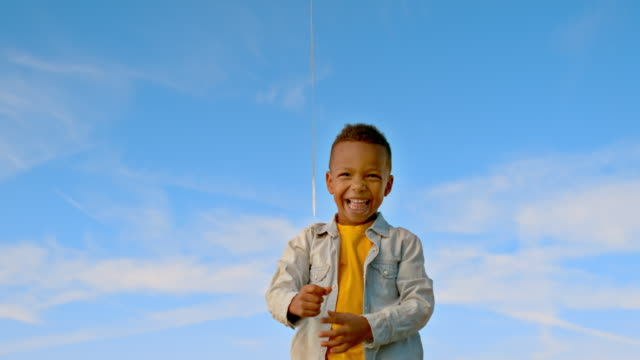 SLO MO Little boy jumping and smiling after letting his balloon float up into the sky Slow motion wide handheld shot of a small boy letting his balloon float up into the sky and jumping and smiling. Shot in Slovenia. one boy only stock videos & royalty-free footage