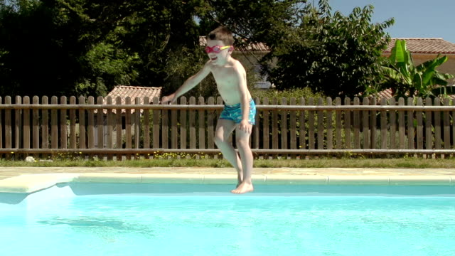 little boy jumping into an outdoor swimming pool not afraid of the water - solo un bambino maschio video stock e b–roll