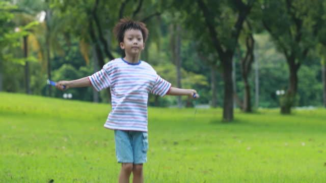 stockvideo's en b-roll-footage met kleine jongen springen touw op gras - touw