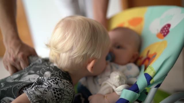 自宅で彼の小さな新生児の弟にキス小さな男の子 - 兄弟姉妹点の映像素材/bロール