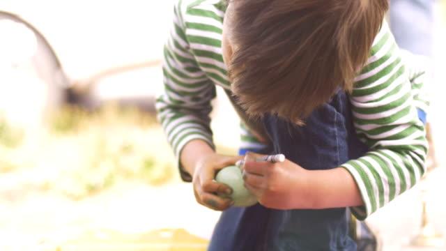 bambino inginocchiato e colorando un uovo di pasqua con un pastello - matita colorata video stock e b–roll