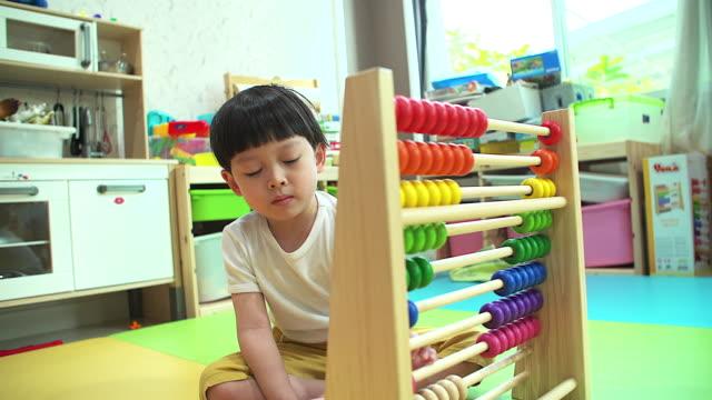 4k: liten pojke lärande genom att räkna med abacus i sitt hem. - abakus bildbanksvideor och videomaterial från bakom kulisserna