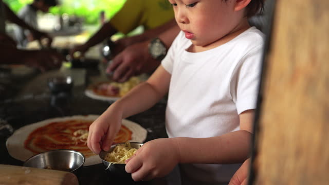 4K: Little boy learning how to make pizza. video