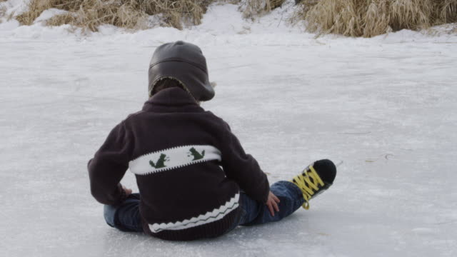 Little Boy Learning to Ice Skate on a Pond Outside video