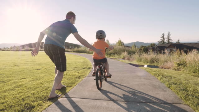 vídeos de stock e filmes b-roll de little boy learning to ride his bike - together