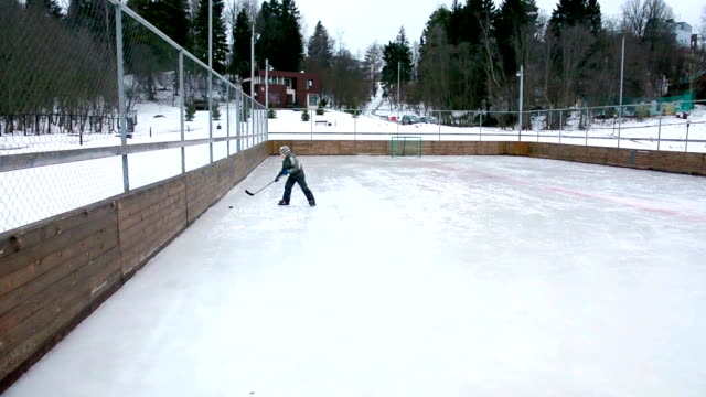 little boy learns to play hockey at winter day on ice rink - hockey stock videos and b-roll footage