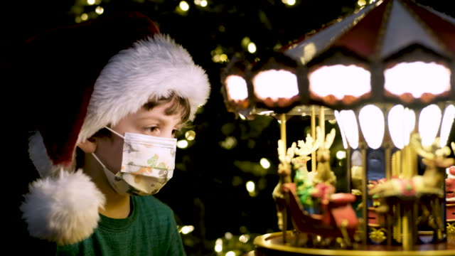 Little boy looking at a toy carrousel wearing a Santa hat and a protective face mask