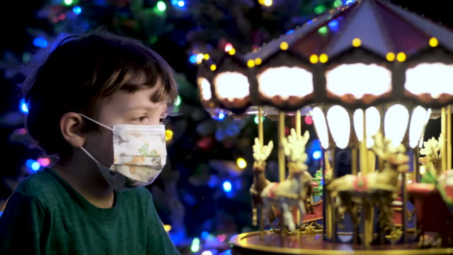 Little boy looking at a toy carrousel wearing aprotective face mask