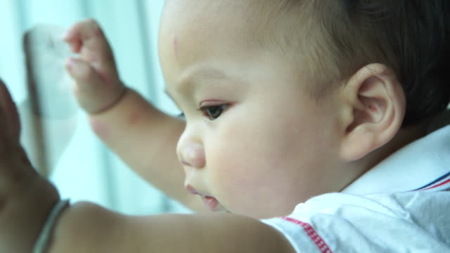 little boy looking at scene out of window - vídeo