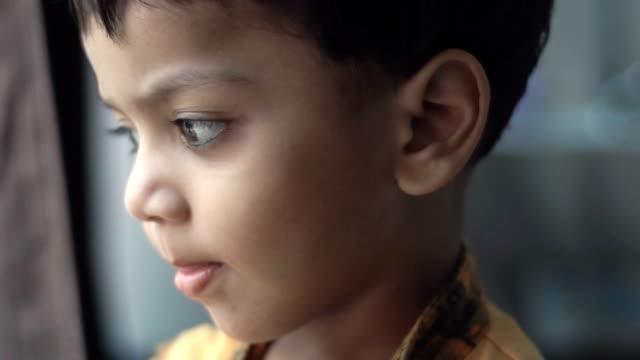 vídeos de stock e filmes b-roll de a little boy looking away with blank expressions - crianças todas diferentes