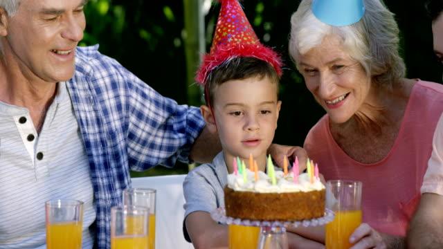 vidéos et rushes de un petit garçon à la recherche de son gâteau d'anniversaire - fête de naissance