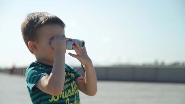 Little Boy Looking Through Binoculars Little Boy Looking Through Binoculars While Playing on the River Embankment in Summer Day. Travel and Adventure concept only boys stock videos & royalty-free footage