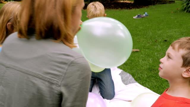 vídeos de stock, filmes e b-roll de um menino olha para a câmera como a mãe dele explode seu balão - slowmo - gênero humano