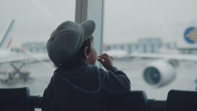 stockvideo's en b-roll-footage met een kleine jongen kijkt naar de vliegtuigen op de luchthaven. - raam bezoek