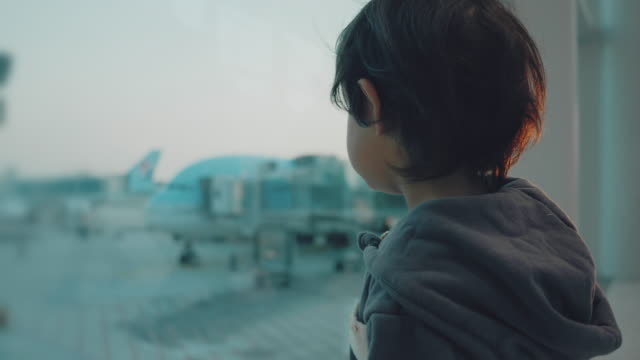 a little boy looks at the planes at the airport. - arrivo video stock e b–roll