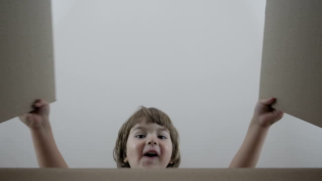 liten pojke ser i rutan, förvånad och glad att få en överraskning. barn öppnade en låda med en gåva. slow motion. leverans order i firandet födelsedag. holiday present jul för kid. - christmas present bildbanksvideor och videomaterial från bakom kulisserna