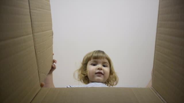 en liten pojke ser ut i rutan, är överraskad och glad att få en överraskning. barnet öppnas en ruta med en gåva. slow motion. internet shopping. - människohuvud bildbanksvideor och videomaterial från bakom kulisserna