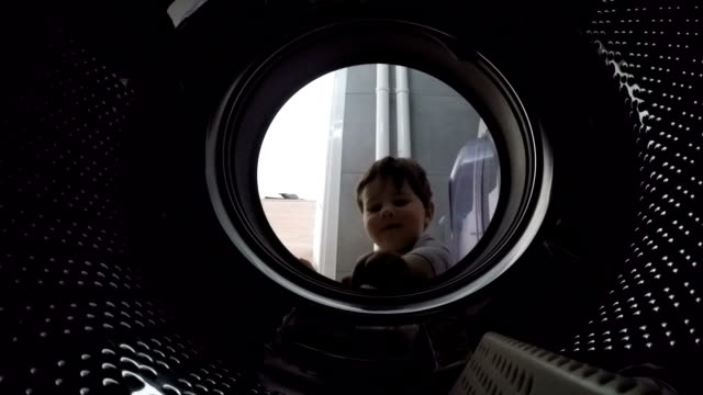 Little boy looks into the empty drum washing machine video