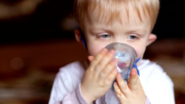 Little boy making inhalation with a nebulizer. video