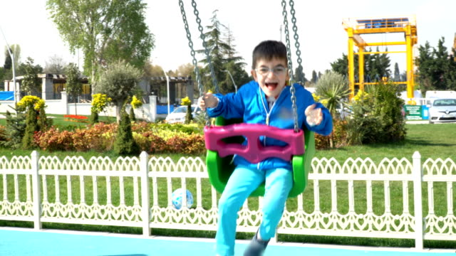 4K Little boy on a swing - Stock video Child, Swing, Swinging, Family, Laughing, Autism, Happy autism stock videos & royalty-free footage