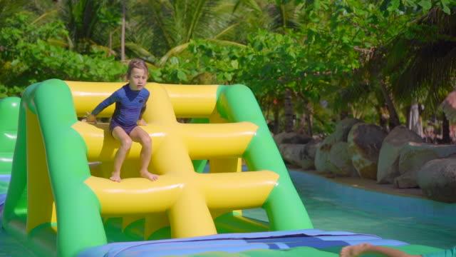 vídeos de stock, filmes e b-roll de little boy em uma pista de obstáculos infláveis em um parque aquático. conceito de verão. tiro de câmera lenta - inflável