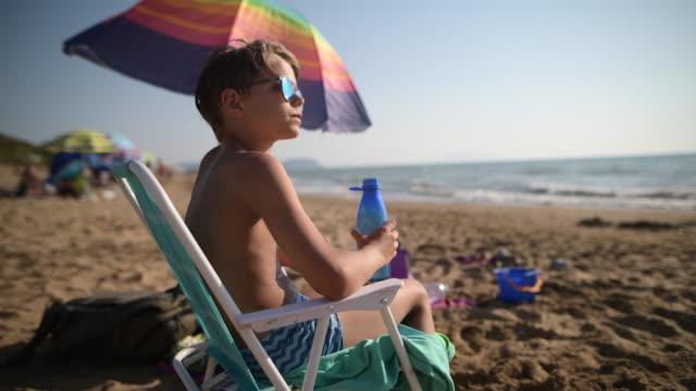 Little boy on beach drinking from reusable water bottle.
