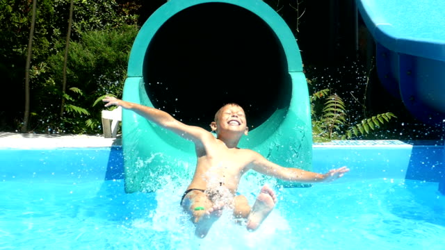 little boy on the water slides in the water park (slow motion) - scivolo video stock e b–roll