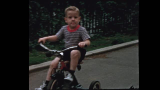 liten pojke på trehjuling slutar ge mamma en kyss - sentimentalitet bildbanksvideor och videomaterial från bakom kulisserna