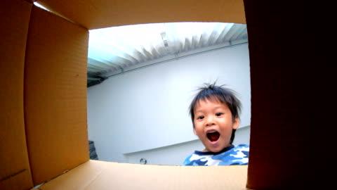 vidéos et rushes de slo mo petit garçon, ouverture de boîte-cadeau. - cadeau