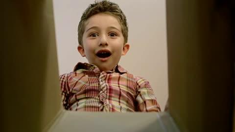 vidéos et rushes de petit garçon ouvre une boîte de parcelle avec différentes versions d'émotions et d'être surpris. - cadeau