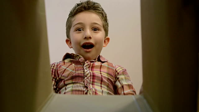 little boy opens a parcel box with different versions of emotions and being surprised. - giocattolo video stock e b–roll