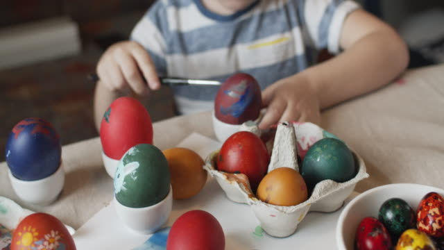 Little boy painting on Easter eggs