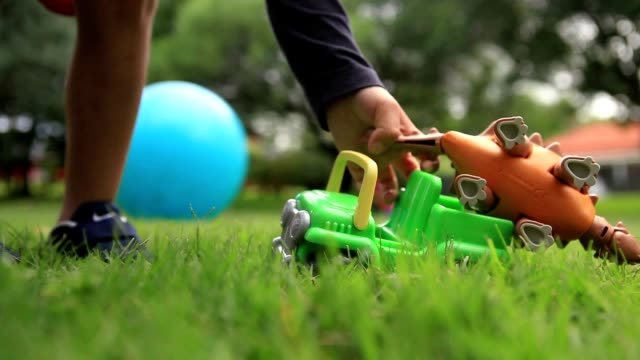 little boy picks up toy car - vitamin d стоковые видео и кадры b-roll