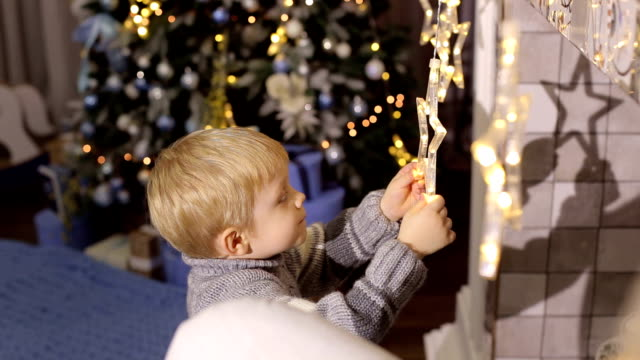 Little boy play with Christmas toys near fireplace video