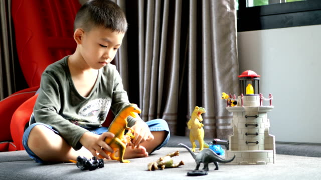 Little Boy playing Animal and Dinosaur on sofa.
