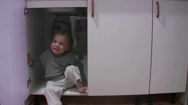 Little boy playing in kitchen cabinet A video of a little boy playing in the cabinets under the sink. cabinet stock videos & royalty-free footage