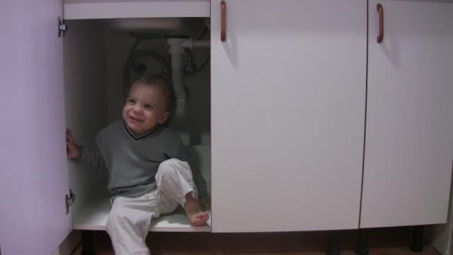 little boy playing in kitchen cabinet - looking inside inside cabinet bildbanksvideor och videomaterial från bakom kulisserna