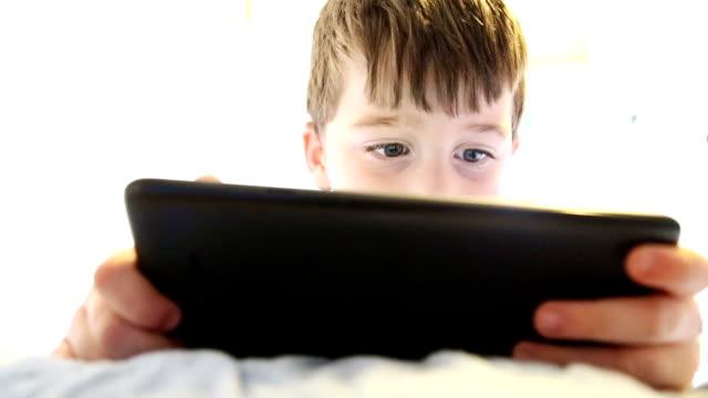 liten pojke som spelar på tablett i sängen - digital reading child bildbanksvideor och videomaterial från bakom kulisserna