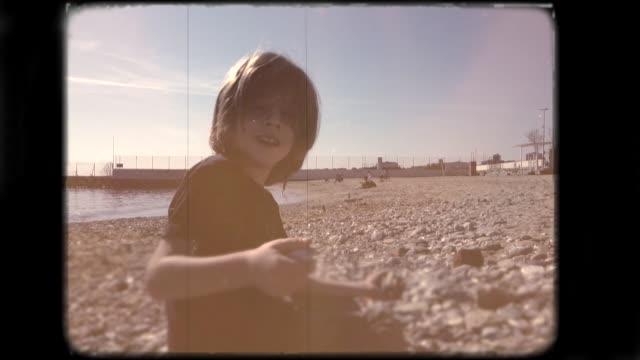 liten pojke som leker på stranden. 8mm film. - sentimentalitet bildbanksvideor och videomaterial från bakom kulisserna