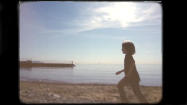 Little boy playing on the beach. 8mm footage.