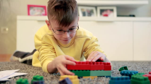 little boy playing on the livingroom floor with blocks set - lego stok videoları ve detay görüntü çekimi