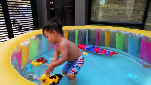 vídeos de stock, filmes e b-roll de garoto jogando o brinquedo na piscina inflável - inflável