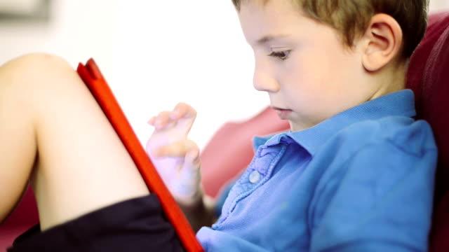 little boy playing with digital tablet - dijital yerli stok videoları ve detay görüntü çekimi