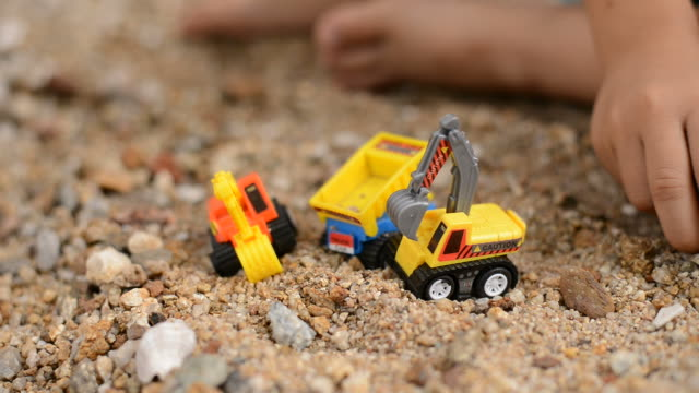 Little Boy Playing with Plastic Toy Excavator on the Sand Beach