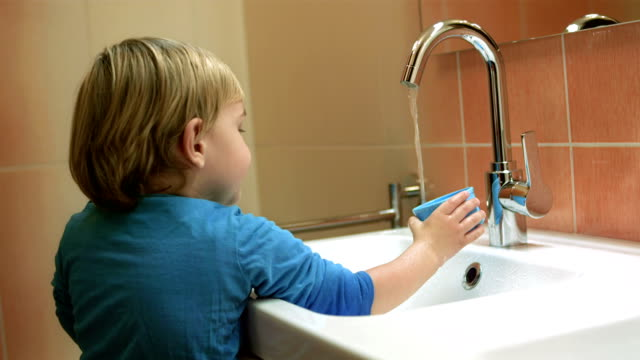 Little Boy Playing With Running Water video
