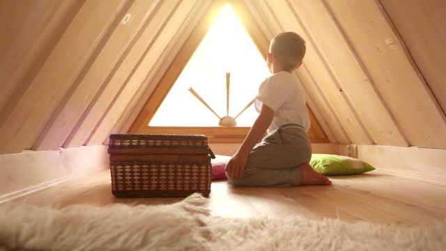 kleiner junge spielt auf dem dachboden, sieht seine eltern nach hause kommen und wellen zu ihnen durch das fenster - dachboden stock-videos und b-roll-filmmaterial