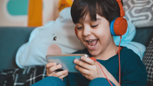 Little boy plays mobile games. Happily playing games with his phone. He uses headphones to avoid being disturbed. Five year old boy playing video game on mobile phone. Preschooler plays game on gadget.