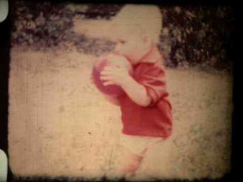 vidéos et rushes de petit garçon jouant avec un ballon, années 1960, 8 mm film - image teintée